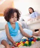 Ragazza nel salone che gioca con i blocchetti del giocattolo Fotografia Stock Libera da Diritti