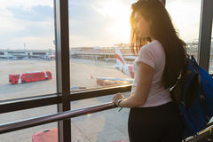 Ragazza nel salotto dell'aeroporto che guarda nella donna felice aspettante piana di sorriso di partenza della finestra Immagini Stock Libere da Diritti