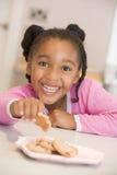 Ragazza nel sorridere dei biscotti di cibo della cucina Fotografia Stock Libera da Diritti