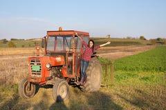 Ragazza nel trattore su terreno coltivabile Fotografie Stock