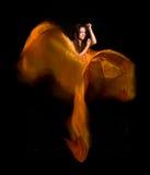 Ragazza nel vestito arancione dal tessuto di volo Fotografie Stock