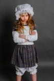 Ragazza nell'annata rustica del vestito su un fondo grigio Fotografie Stock