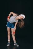 Ragazza nell'esercitazione degli abiti sportivi isolata sul nero Fotografie Stock Libere da Diritti