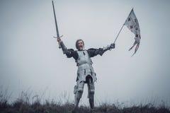 Ragazza nell'immagine dei supporti dell'arco del ` di Jeanne d in armatura e nel grido di battaglia delle edizioni con la spada a immagine stock