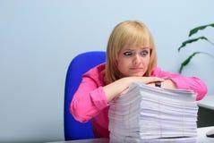 Ragazza nell'ufficio che esamina disperatamente la pila di documenti Fotografie Stock Libere da Diritti