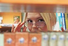 Ragazza nella biblioteca con i vetri che guardano da dietro Fotografia Stock Libera da Diritti