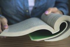 Ragazza nella camicia blu del denim che legge un libro di libro in brossura Fotografie Stock