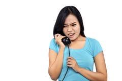 Ragazza nella conversazione arrabbiata di sembrare blu della camicia sul telefono Immagine Stock