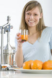 Ragazza nella cucina con l'arancio sugoso Immagine Stock