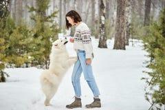 Ragazza nella foresta di inverno che cammina con un cane La neve sta cadendo fotografie stock