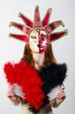 Ragazza nella maschera con un fan in mani Immagini Stock