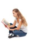 Ragazza nella posizione di loto per leggere il libro Immagine Stock