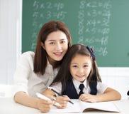 Ragazza nella scrittura della classe con l'aiuto dell'insegnante Immagine Stock