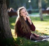 Ragazza nella seduta sorridente del cappotto su un plaid nel parco di autunno fotografia stock libera da diritti