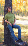 Ragazza nella sosta di autunno vicino all'albero Fotografia Stock