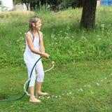 Ragazza nella spruzzatura bianca con il tubo flessibile di giardino Fotografie Stock