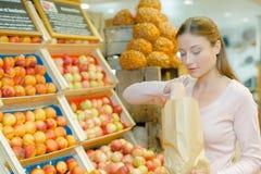 Ragazza nella stalla della frutta Immagini Stock