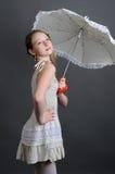 Ragazza nelle prendisole di tela con l'ombrello di sole Fotografia Stock