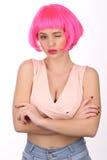 Ragazza nello sbattere le palpebre rosa della parrucca Fine in su Priorità bassa bianca Immagini Stock