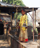 Ragazza nepalese che gioca la campana in tempio indù Fotografie Stock