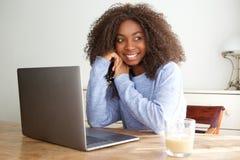 Ragazza nera che si siede ad una tavola con il computer portatile che distoglie lo sguardo e che sorride Fotografia Stock Libera da Diritti