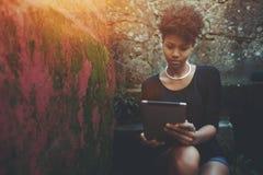 Ragazza nera dello studente non laureato sul punto della scala con il cuscinetto digitale Fotografie Stock Libere da Diritti