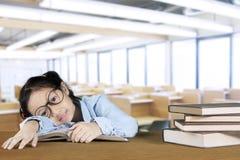 Ragazza nerd che dorme con un mucchio dei libri Immagini Stock Libere da Diritti