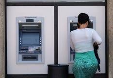 Ragazza non identificata che ritira soldi da una macchina di BANCOMAT Immagine Stock