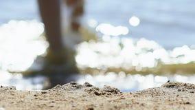 Ragazza nuda lenta che cammina dalla secca dell'oceano, fine dei piedi delle gambe su archivi video