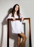 Ragazza nuda in una camicia bianca del ` s dell'uomo che tiene struttura di legno Fotografia Stock Libera da Diritti