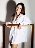 Ragazza nuda in una camicia bianca del ` s dell'uomo che tiene struttura di legno Fotografie Stock