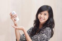 Bella ragazza asiatica che usando lozione per preoccuparsi la sua pelle immagini stock libere da diritti