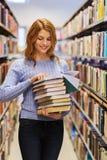 Ragazza o donna felice dello studente con i libri in biblioteca Fotografia Stock Libera da Diritti