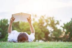 Ragazza o studenti abbastanza asiatici che legge un libro nel parco pubblico Immagine Stock