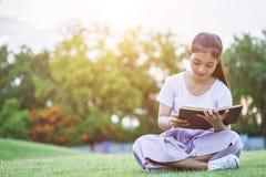 Ragazza o studenti abbastanza asiatici che legge un libro nel parco pubblico Fotografia Stock
