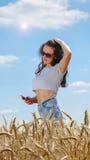 Ragazza in occhiali da sole con il telefono cellulare Fotografia Stock Libera da Diritti