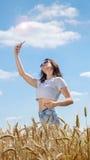 Ragazza in occhiali da sole con il telefono cellulare Fotografie Stock Libere da Diritti