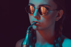 Ragazza in occhiali da sole rotondi che beve soda dalla bottiglia di acqua con paglia Fotografia Stock Libera da Diritti