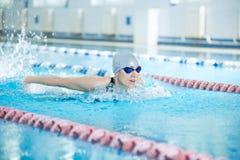 Ragazza in occhiali di protezione che nuota stile del colpo di farfalla Immagini Stock
