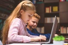 Ragazza occupata che per mezzo del suo computer portatile Fotografia Stock Libera da Diritti