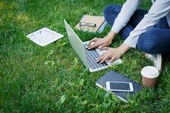 Ragazza occupata delle free lance che lavora con il computer portatile nel parco durante il giorno Fotografie Stock