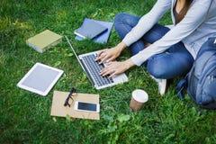 Ragazza occupata delle free lance che lavora con il computer portatile nel parco durante il giorno Immagine Stock Libera da Diritti