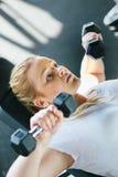 Ragazza paffuta del principiante che si esercita nel club di forma fisica Fotografia Stock