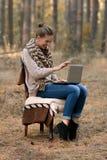 Ragazza pazza, felice, allegra con il bello lavoro al computer portatile, computer di sorriso nella foresta, all'aperto in buon t Fotografie Stock