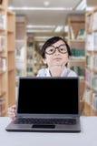 Ragazza pensierosa con il computer portatile in biblioteca Fotografia Stock Libera da Diritti