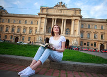 Ragazza pensierosa dello studente con il libro su fondo dell'università Fotografia Stock Libera da Diritti