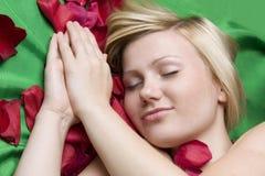 Ragazza in petalo di rosa su priorità bassa verde immagine stock libera da diritti