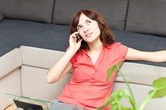 Ragazza piacevole che comunica il telefono vicino alla tabella Immagini Stock