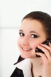 Ragazza piacevole che comunica sul telefono Immagine Stock