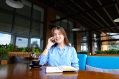Ragazza piacevole che riposa al caffè con il taccuino e la tazza di caffè, parlanti dallo smartphone Immagini Stock Libere da Diritti